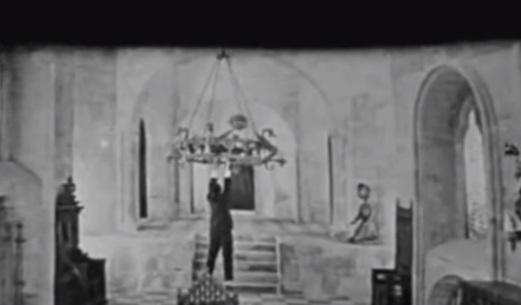 Au Secours chandelier scene